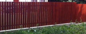 Sztacheta drewniana ze schowanymi (znajdującymi się z tyłu ogrodzenia) słupkami metalowymi. To nowoczesna forma ogrodzenia sztachetowego drewnianego